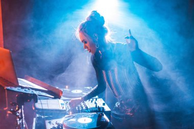concentrated dj woman with blonde hair gesturing and using dj equipment in nightclub with smoke
