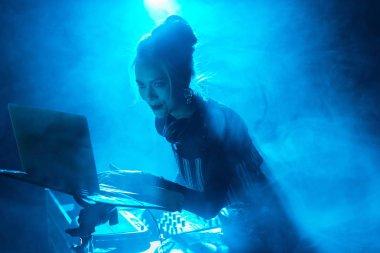 happy dj woman with blonde hair using laptop near dj equipment in nightclub with smoke
