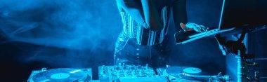 panoramic shot of dj woman using laptop in nightclub with smoke