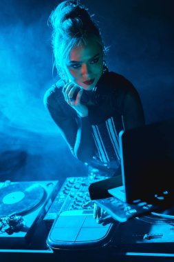 serious dj woman with blonde hair looking at laptop in nightclub with smoke