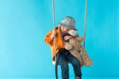 Fotografie cute child sitting on swing and hugging teddy bear isolated on blue
