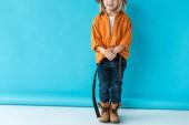 oříznutý pohled kid v džínách a oranžové tričko na modrém pozadí