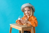 Fotografie kid in silver hat and orange shirt holding aquarium with goldfish isolated on blue