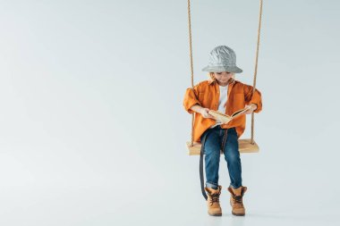 cute kid in jeans and orange shirt sitting on swing and reading book on grey background