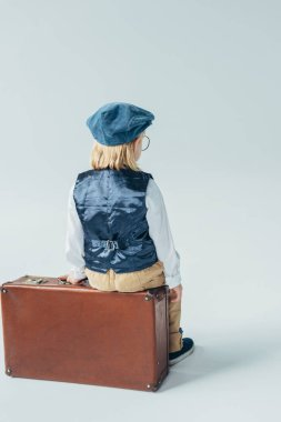 Back view of kid in retro vest and cap sitting on suitcase on grey background stock vector