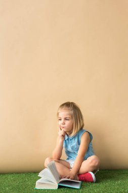 pensive child sitting with crossed legs on grass rug and holding book on beige background