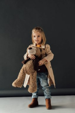 Smiling and cute child in trench coat and jeans holding teddy bear on black background stock vector