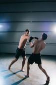Fotografie starke barfuß Mma Sportler kämpfen beim Stanzen einen anderen Mann