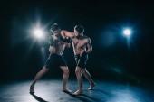 Fotografie MMA-Kämpfer Stanzen ein weiterer Sportler beim Muay thai training