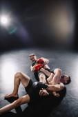 silné shirtless mma bojovník dělat bolestivé společné zámek na jiný sportovec zároveň člověk křičí na podlaze