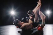 silná mma bojovník v Boxerské rukavice dělají bolestivé chokehold s nohama na jiný sportovec na podlaze