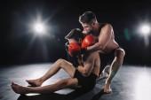 silná mma bojovník v Boxerské rukavice dělá chokehold na jiný sportovec na podlaze