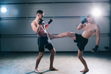 side view of muscular barefoot mma fighter kicking sportive opponent with leg