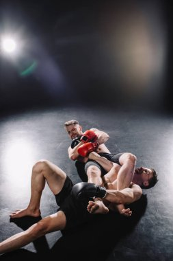 strong shirtless mma fighter doing painful joint lock to another sportsman while man screaming on floor
