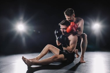 Strong mma fighter in boxing gloves doing painful chokehold to another sportsman on floor stock vector