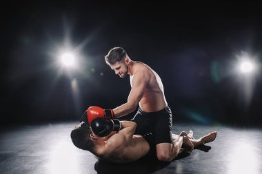 Strong mma fighter in boxing gloves sitting on opponent and punching him in head while sportsman lying on floor stock vector