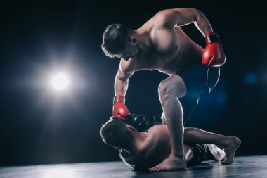 bottom view of strong mma fighter in boxing gloves punching opponent in head while sportsman lying on floor