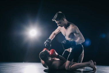 Shirtless strong mma fighter in boxing gloves standing on knees above opponent and punching him stock vector