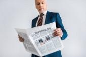 Selektivní fokus zralých podnikatel čtení obchodní noviny izolované Grey