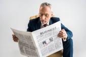 starší podnikatel v brýlích a oblek čtení obchodní noviny izolované Grey