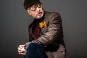 divatos és töprengő érett férfi sapka és szürke szemüveg
