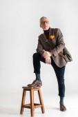 divatos érett férfi elhelyezés lábát a székre állva szürke