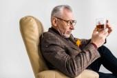 érett férfi ül a karosszékben és látszó-on pohár whiskyt elszigetelt szürke