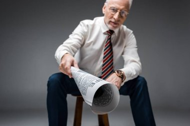 Selective focus of newspaper in hand of mature businessman on grey stock vector