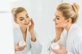 szelektív összpontosít, vonzó és mosolygós nő a fehér fürdőköpeny alkalmazása a fürdőszobában arckrém