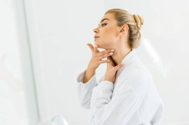 attractive and blonde woman in white bathrobe applying face cream in bathroom