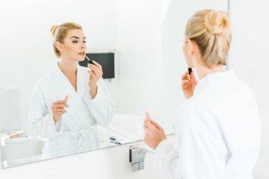 selective focus of woman in white bathrobe applying lip gloss in bathroom