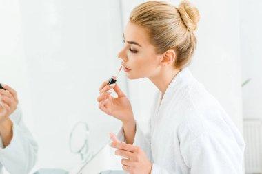 selective focus of beautiful woman in white bathrobe applying lip gloss in bathroom