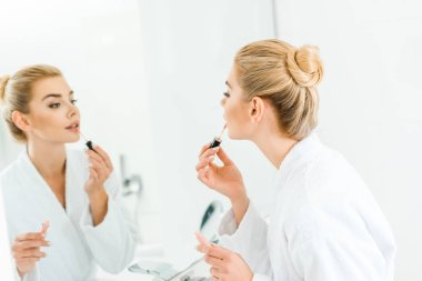 selective focus of beautiful and blonde woman in white bathrobe applying lip gloss in bathroom