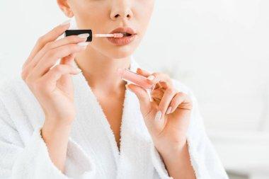 cropped view of woman in white bathrobe applying lip gloss in bathroom