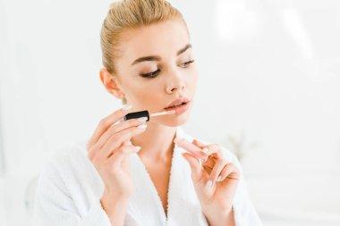 beautiful and blonde woman in white bathrobe applying lip gloss in bathroom