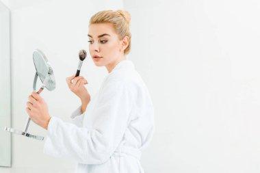 beautiful and blonde woman in white bathrobe using cosmetic brush in bathroom