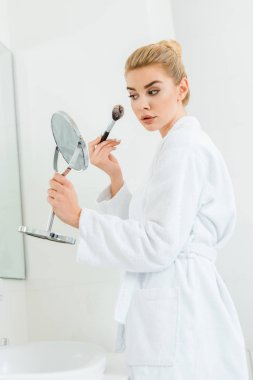 attractive and blonde woman in white bathrobe using cosmetic brush in bathroom