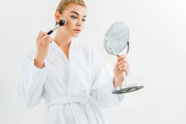 attractive and blonde woman in white bathrobe using cosmetic brush and holding mirror