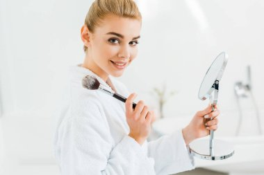 attractive and blonde woman in white bathrobe holding cosmetic brush and looking at camera