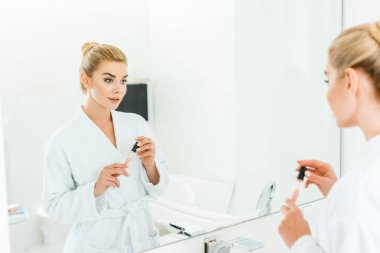 selective focus of beautiful woman in white bathrobe holding lip gloss in bathroom