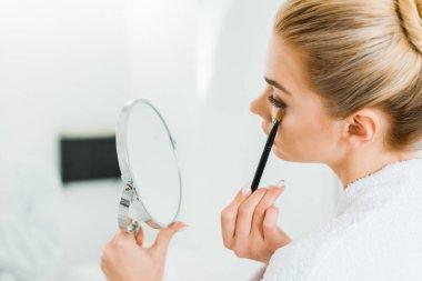 selective focus of woman in white bathrobe applying eyeshadow with cosmetic brush in bathroom