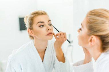 selective focus of woman in white bathrobe applying eyeshadow with cosmetic brush