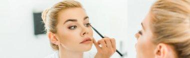 panoramic shot of blonde and beautiful woman applying eyeshadow with cosmetic brush