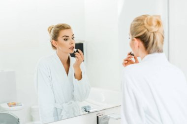 selective focus of woman in white bathrobe applying lipstick and looking at mirror in bathroom