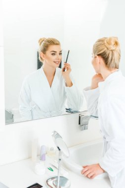 selective focus of woman in white bathrobe holding cosmetic brush in bathroom