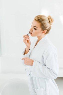 beautiful and blonde woman in white bathrobe applying lipstick in bathroom