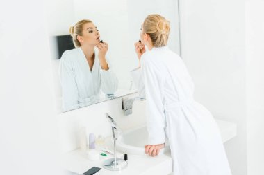 selective focus of beautiful and blonde woman in white bathrobe applying lipstick in bathroom