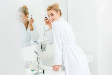 selective focus of beautiful and smiling woman in white bathrobe holding lipstick and looking at camera