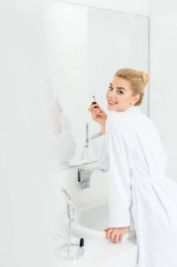 beautiful and smiling woman in white bathrobe holding lipstick and looking at camera
