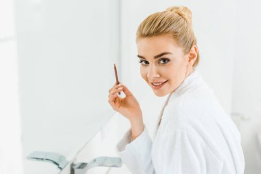 beautiful and smiling woman in white bathrobe holding lip liner and looking at camera